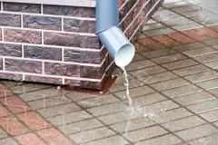 brick wall with a drainpipe in rain